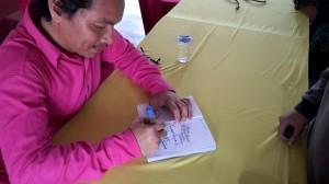 Sesi menandatangani autograf